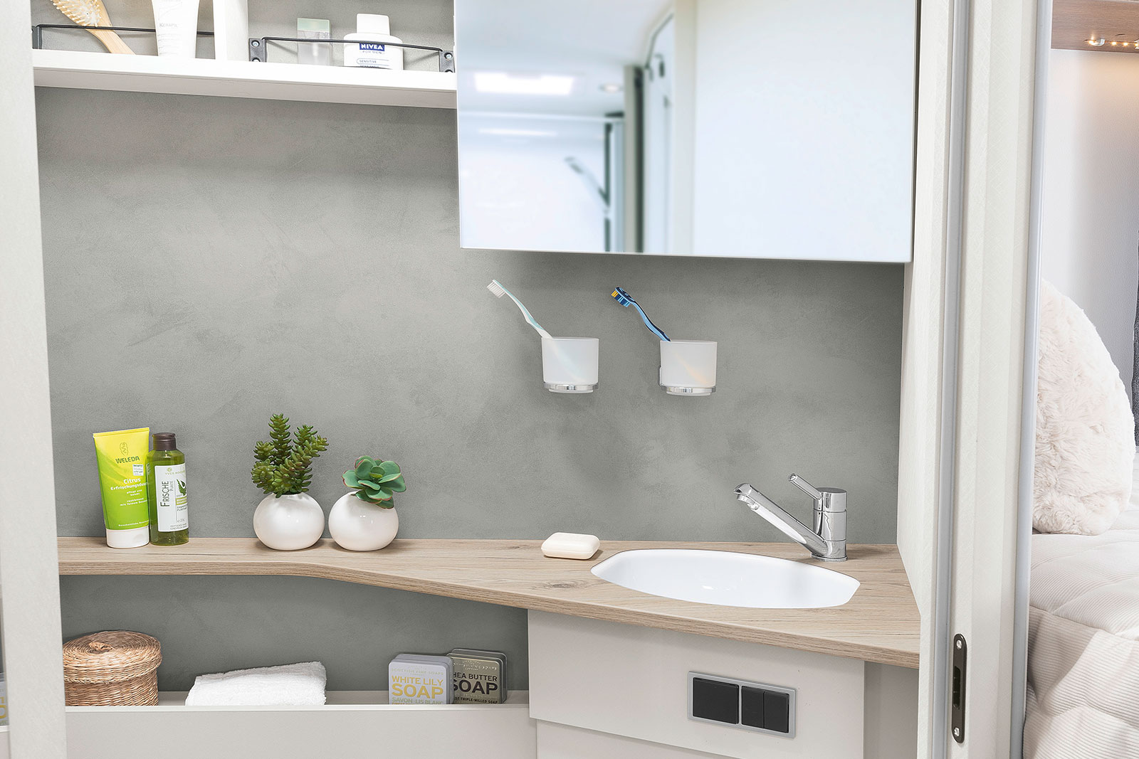 Bright and modern toilet room with practical side-sliding mirror and many storage and stowage possibilities • I 7057 EB